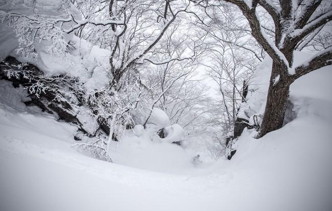 Kelsey slides through a narrow rocky chute somewhere in Nozawa Onsen.